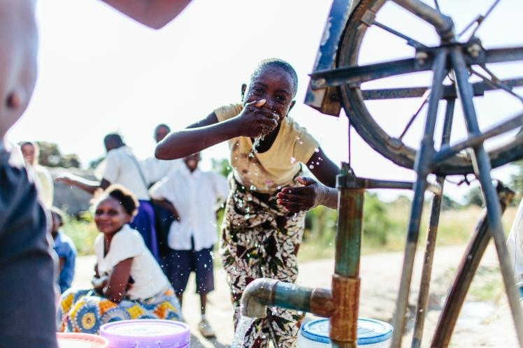 Girl washing her face at hand held pump, Tanzania.jpg